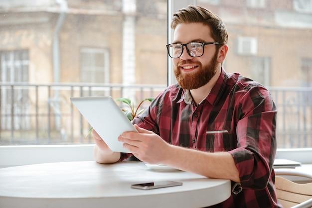 Jovem barbudo bonito usando computador tablet.