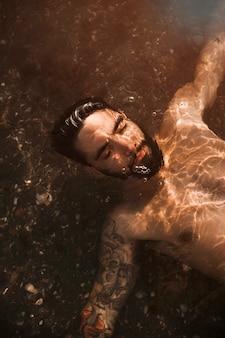 Jovem barbudo cara deitado debaixo de água na praia