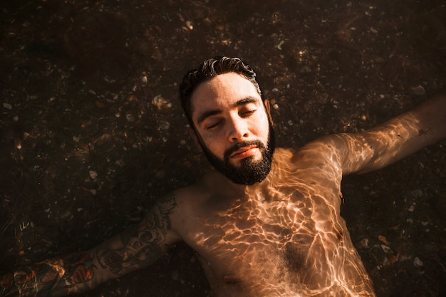 Jovem barbudo cara deitado na água na praia