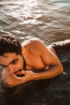 Jovem barbudo cara deitado na praia na água