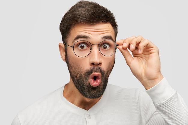 Jovem barbudo chocado mantém os olhos arregalados, olha através dos óculos, imagina notícias repentinas