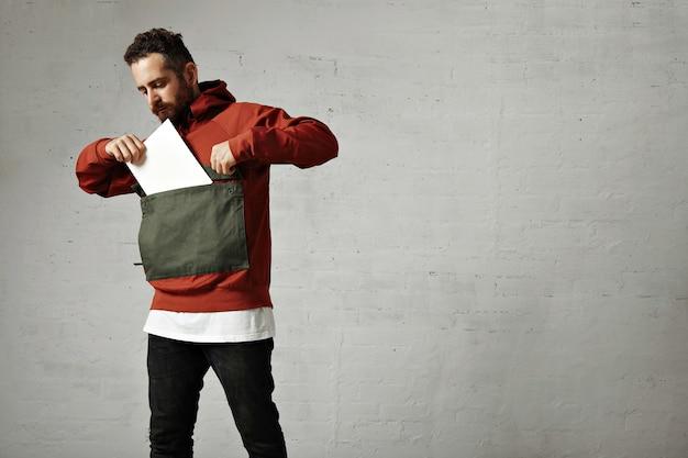 Jovem barbudo colocando uma folha de papel em branco no enorme bolso frontal de seu anoraque vermelho e cinza na parede branca