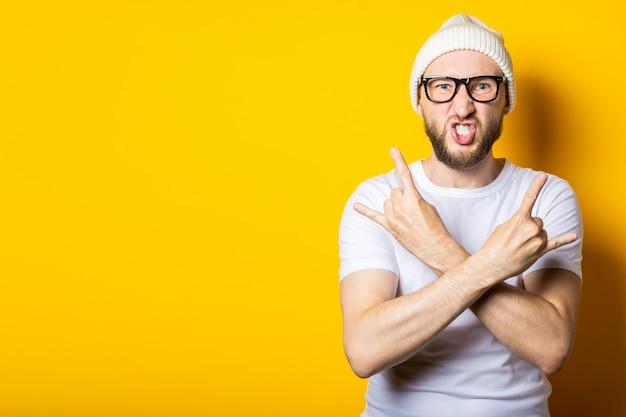 Jovem barbudo com braços cruzados mostra um gesto de cabra roqueira