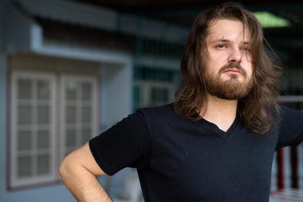 Jovem barbudo com cabelo comprido pensando em casa ao ar livre