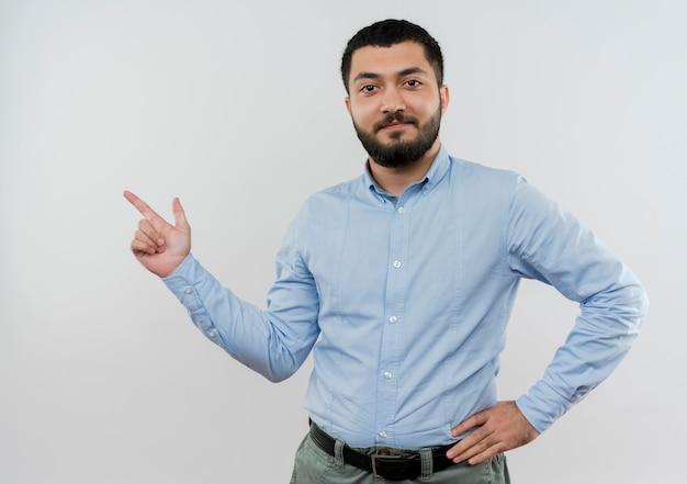 Jovem barbudo com camisa azul apontador com o dedo indicador para o lado e sorrindo confiante em pé sobre uma parede branca