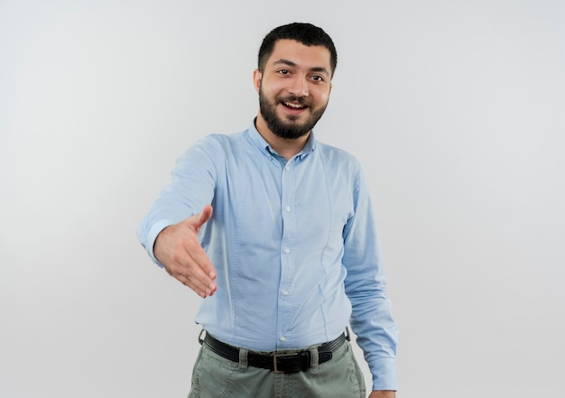 Jovem barbudo com camisa azul sorrindo, oferecendo saudação com a mão e sorrindo amigável