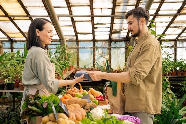 Jovem barbudo com camisa casual pagando com cartão sem contato por produtos orgânicos frescos no mercado de fazendeiros