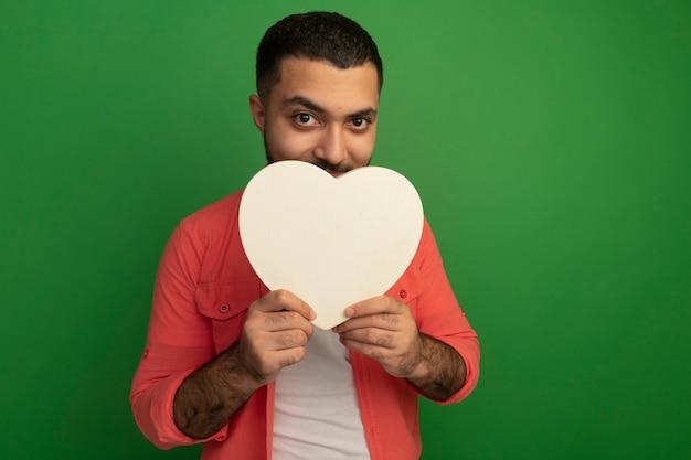 Jovem barbudo com camisa laranja segurando um coração de papelão e sorrindo maliciosamente em pé sobre a parede verde