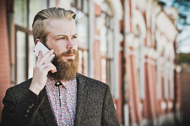 Jovem barbudo com celular, ao ar livre, horário de verão