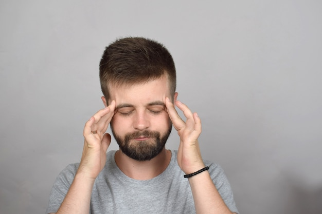 Jovem barbudo com dor de cabeça