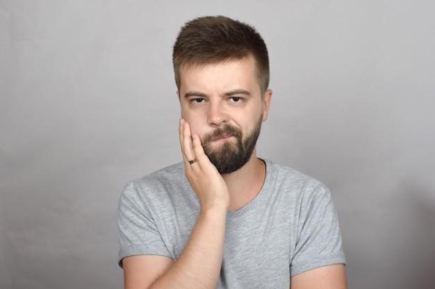 Jovem barbudo com dor de dente