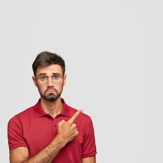 Jovem barbudo com expressão facial descontente, rosto carrancudo, olhar perplexo, aponta para cima, vestido casualmente, encosta-se a uma parede branca