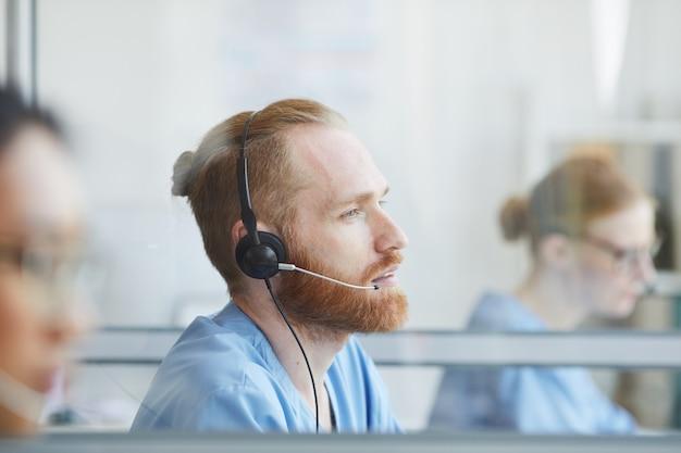 Jovem barbudo com fones de ouvido trabalhando em um call center médico