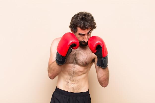 Jovem barbudo com luvas de boxe e conceito de fitness de luta