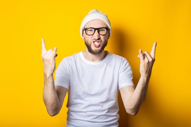 Jovem barbudo com óculos mostra um gesto de cabra roqueira