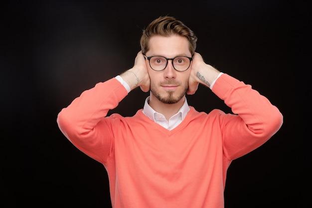 Jovem barbudo com suéter laranja fechando os olhos com as mãos enquanto brinca de esconde-esconde ou fica com medo