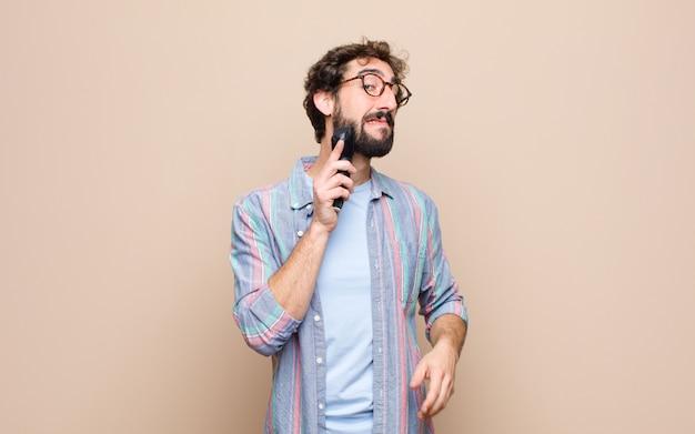 Jovem barbudo com um barbeador elétrico
