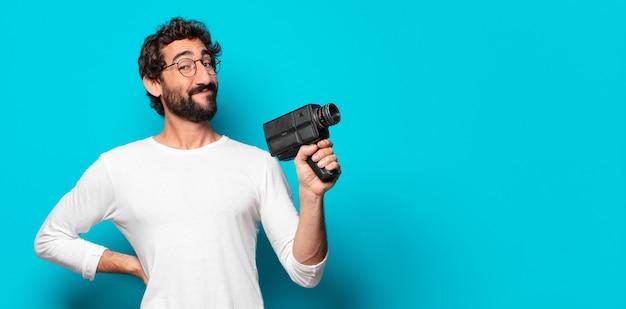 Jovem barbudo com uma câmera de vídeo super 8