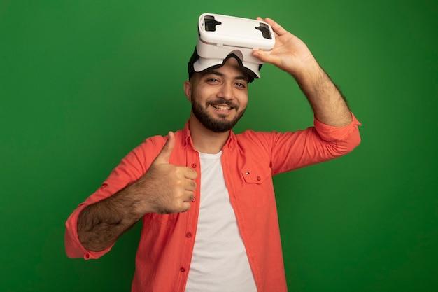Jovem barbudo com uma camisa laranja e óculos de realidade virtual na cabeça aparecendo sorrindo alegremente em pé sobre a parede verde