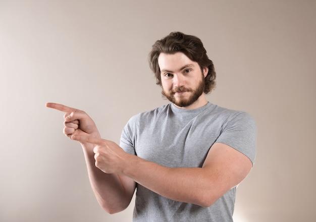 Jovem barbudo com uma camiseta cinza gesticulando com as mãos sobre um fundo cinza claro