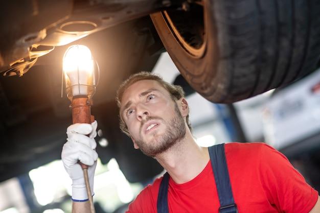 Jovem barbudo com uma lâmpada na mão examinando atentamente o fundo de um carro levantado