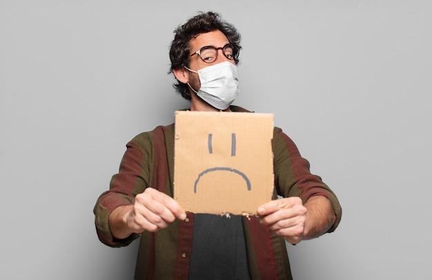 Jovem barbudo com uma máscara médica e o conceito de faixa triste