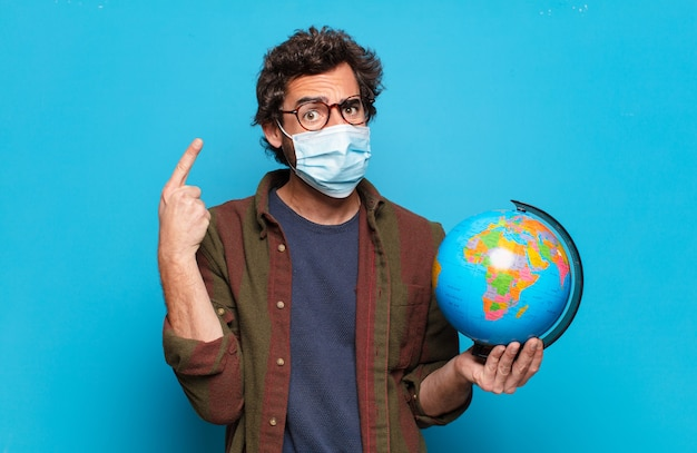 Jovem barbudo com uma máscara médica e um modelo de mapa-múndi