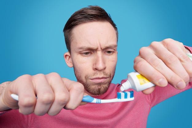 Jovem barbudo concentrado com testa franzida se preparando para escovar os dentes