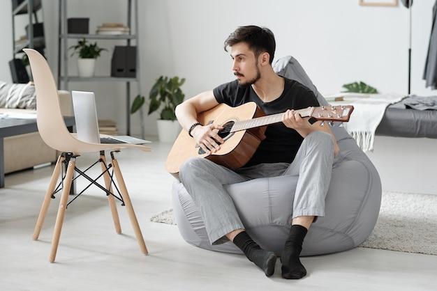 Jovem barbudo concentrado sentado em um saco de feijão e assistindo a um vídeo no laptop enquanto aprende a tocar guitarra