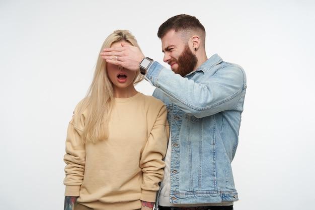 Jovem barbudo confuso com casaco jeans franzindo a testa e os olhos cônicos de sua namorada loira de cabelos compridos espantada em um moletom bege, isolado no branco