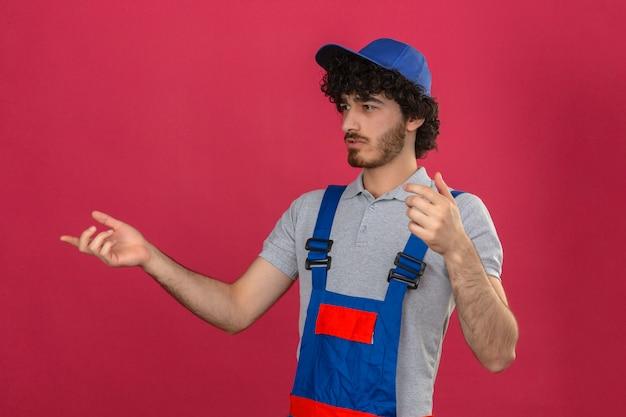 Jovem barbudo construtor bonito vestindo uniforme de construção e capacete de segurança, olhando de lado mexendo com problema de trabalho confuso em pé sobre parede rosa isolada