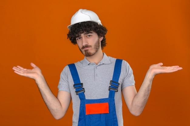 Jovem barbudo construtor bonito vestindo uniforme de construção e capacete de segurança sem noção e confuso com os braços abertos, nenhum conceito de idéia em pé sobre a parede laranja isolada