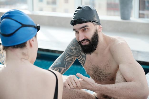 Jovem barbudo contente de touca de natação conversando com a nadadora enquanto torce por ela à beira da piscina