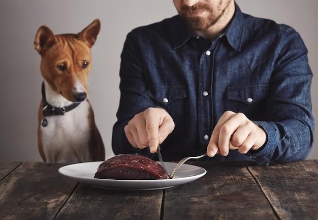 Jovem barbudo corta um pequeno pedaço de grande bife de baleia para compartilhar com seu lindo cachorro africano. o cachorro está observando com atenção.