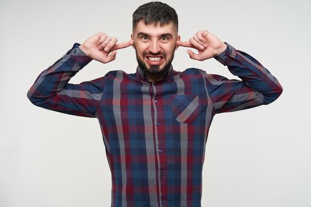 Jovem barbudo, de cabelos curtos, colocando os dedos indicadores nas orelhas enquanto tenta evitar sons altos, em pé sobre uma parede branca