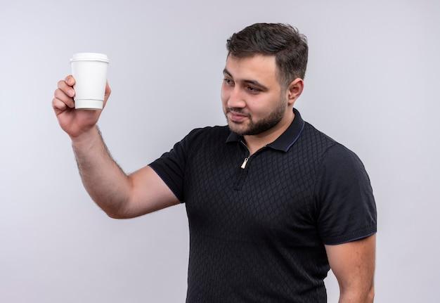Jovem barbudo de camisa preta segurando uma xícara de café, levantando a mão e sorrindo confiante