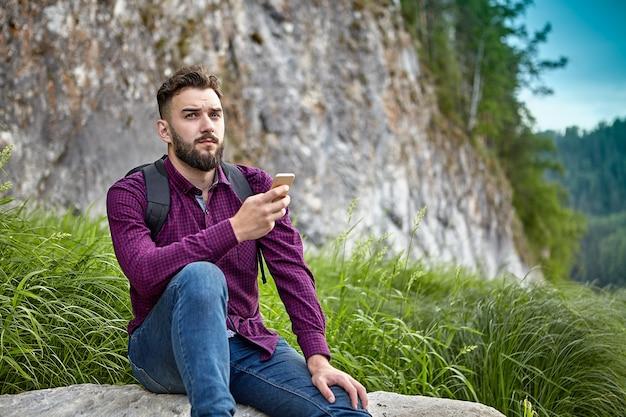 Jovem barbudo de etnia branca segura o smartphone nas mãos, durante aventuras na trilha de caminhada.