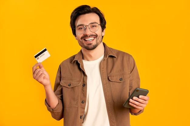 Jovem barbudo de óculos detém cartão de crédito e smartphone isolados. compras online. pagamento online.