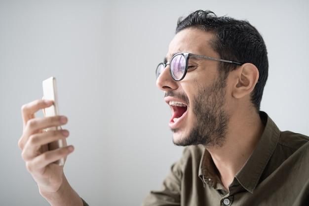 Jovem barbudo de óculos e camisa gritando na frente da câmera do smartphone enquanto faz uma selfie isolado
