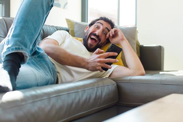 Jovem barbudo descansando em um sofá com seu smartphone