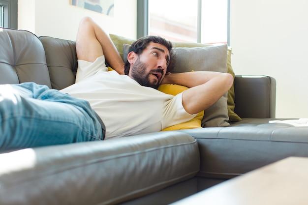 Jovem barbudo descansando em um sofá