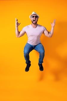 Jovem barbudo e animado, esportivo, com chapéu e óculos de sol, pula emocionalmente isolado no amarelo