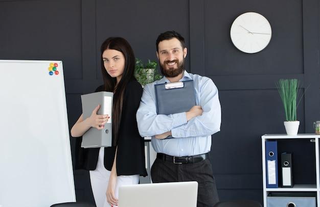Jovem barbudo e uma mulher em trajes formais discutindo algo enquanto seguram uma pasta com documentos
