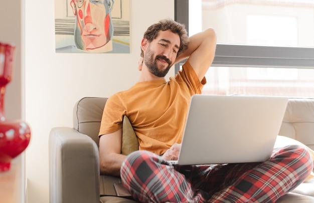 Jovem barbudo em um sofá com um laptop