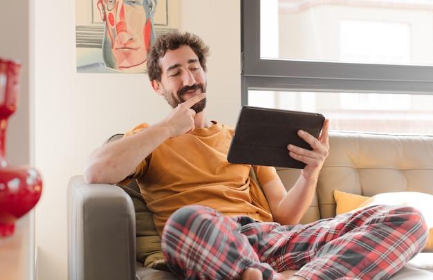 Jovem barbudo em um sofá com um tablet touch screen