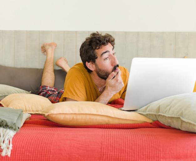 Jovem barbudo em uma cama com um laptop Foto Premium