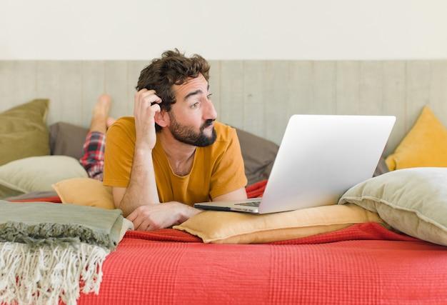 Jovem barbudo em uma cama com um laptop