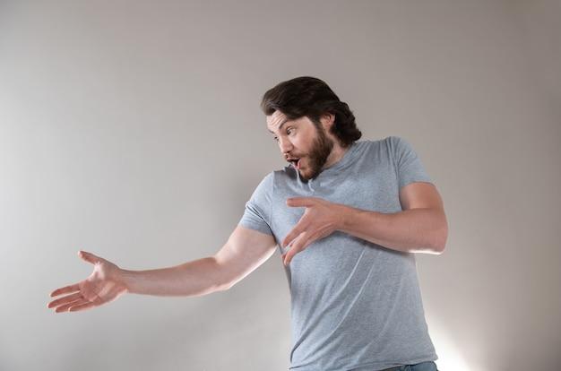 Jovem barbudo emocional surpreso, frustrado e desnorteado homem isolado no fundo cinza do estúdio.