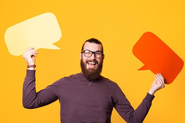 Jovem barbudo empolgado sorrindo e segurando dois balões de fala usando óculos