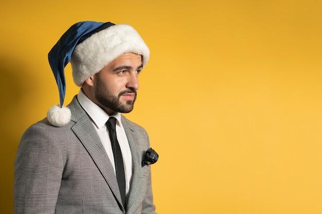 Jovem barbudo encantador com chapéu de papai noel azul e terno cinza, olhando de lado, isolado na parede amarela